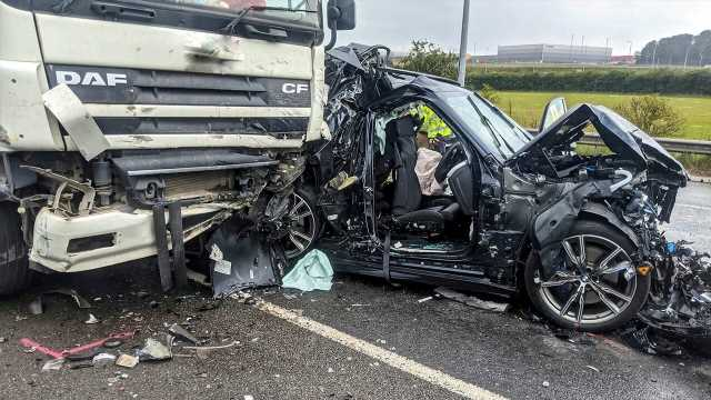 BMW driver survives being crushed between 2 semitrucks