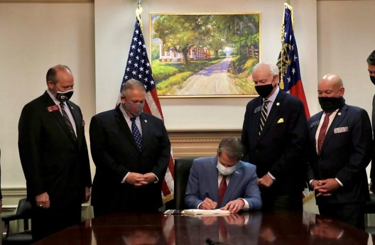 Gov. Brian Kemp signs restrictive Georgia voting bill into law in front of painting of former plantation grounds